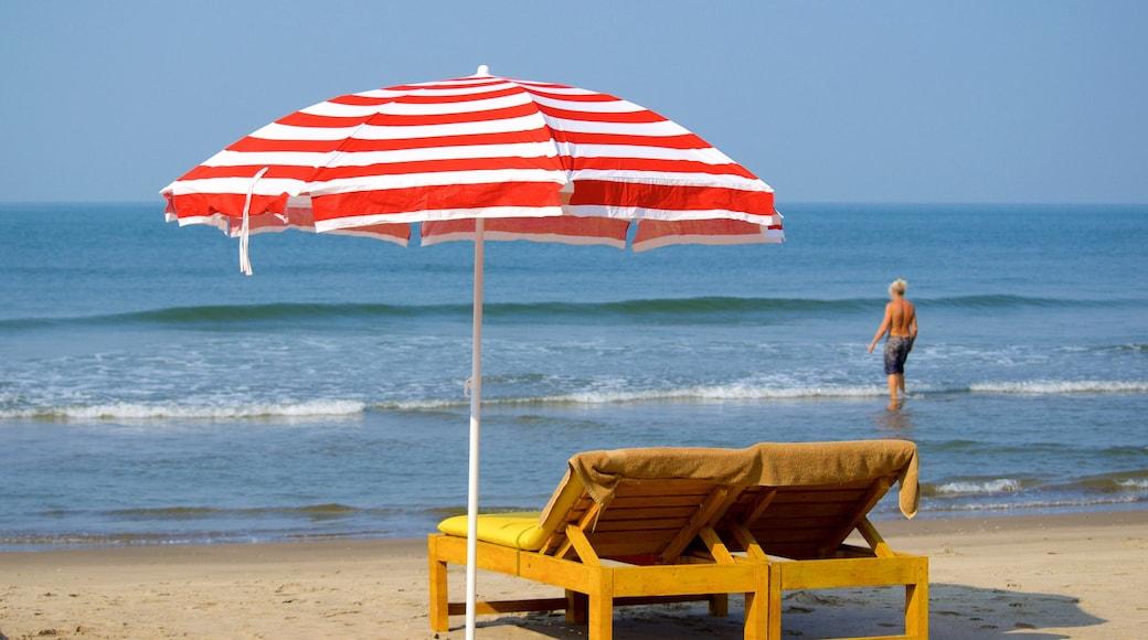 Praia de Vagator mostrando uma praia de areia e paisagens litorâneas assim como um homem sozinho