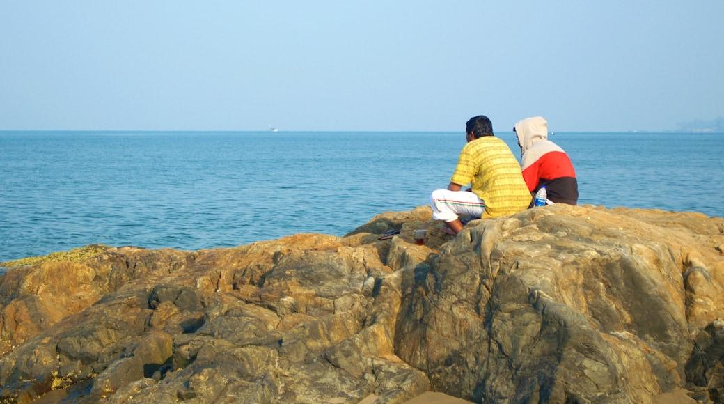 Praia de Vagator mostrando paisagens litorâneas e litoral rochoso assim como um pequeno grupo de pessoas