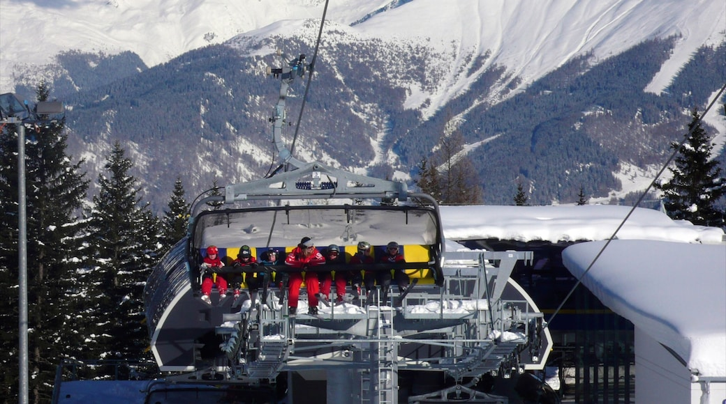 Serfaus which includes a gondola and snow as well as a large group of people