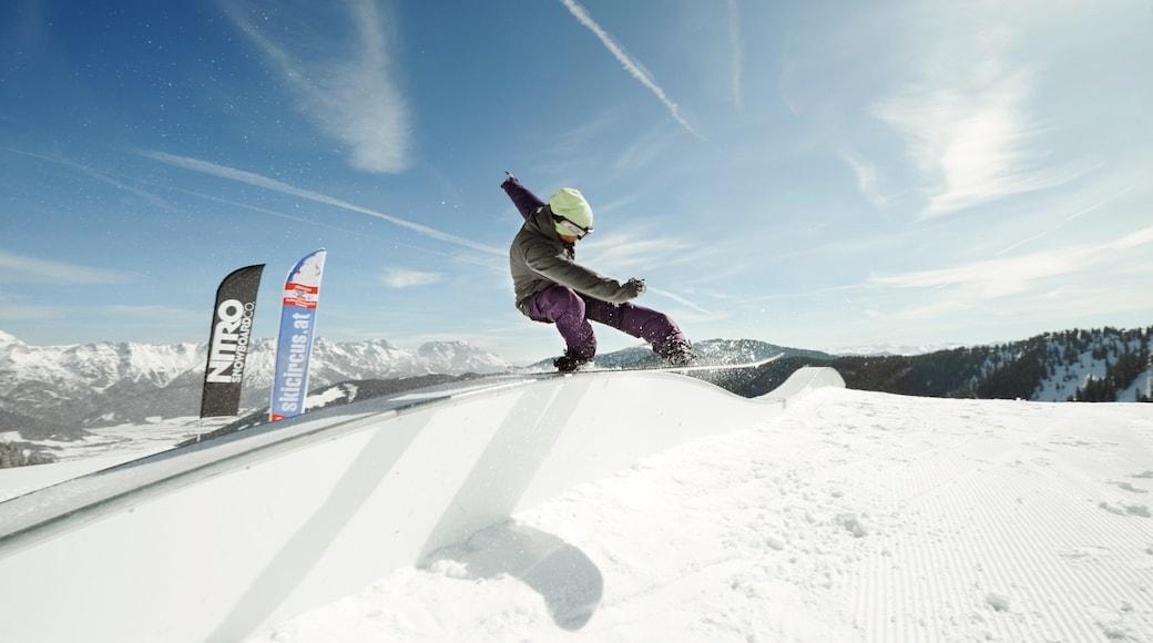 Saalbach-Hinterglemm skiområde som viser snø og snowboarding i tillegg til en mann