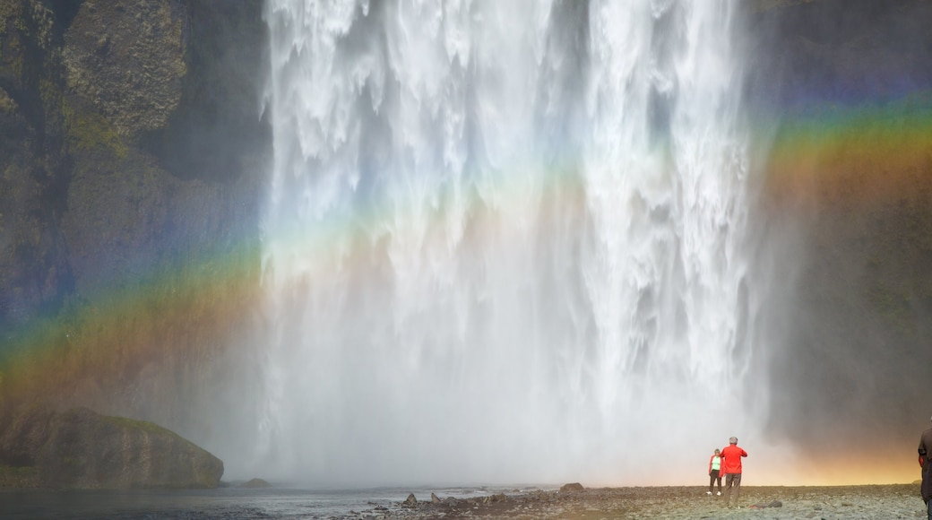 Skogafoss featuring a waterfall as well as a small group of people