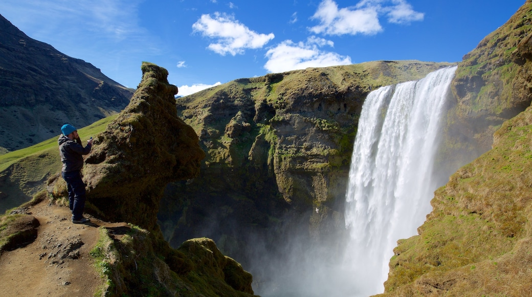 Skogafoss showing a cascade and a gorge or canyon as well as an individual male