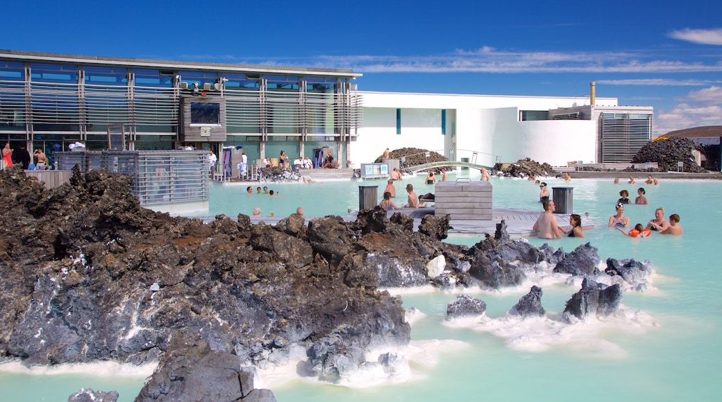 Blue Lagoon showing a hot spring and a luxury hotel or resort as well as a large group of people