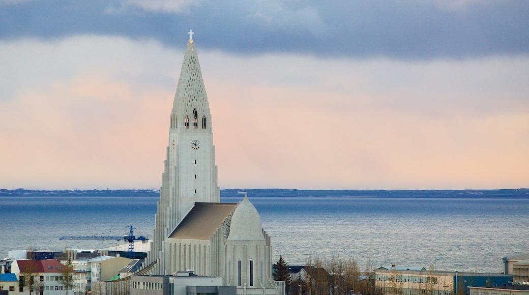 Hallgrímskirkja mostrando vistas generales de la costa, una iglesia o catedral y una puesta de sol