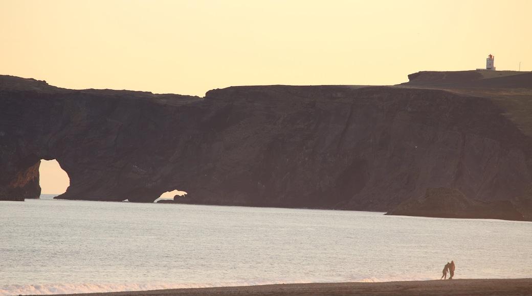 Svarta stranden som inkluderar en solnedgång och kustutsikter