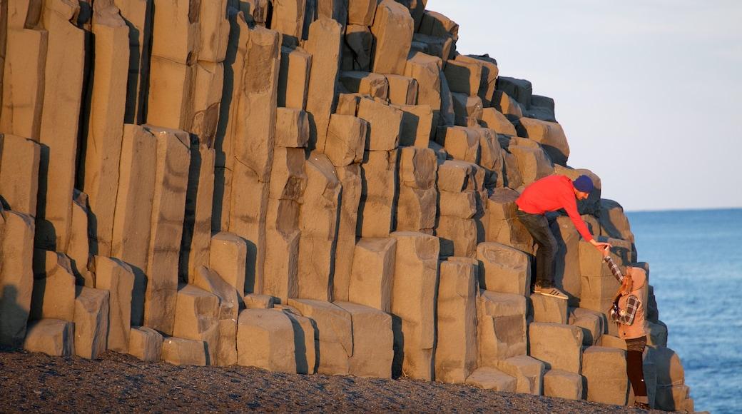 Svarta stranden som inkluderar en solnedgång såväl som en liten grupp av människor