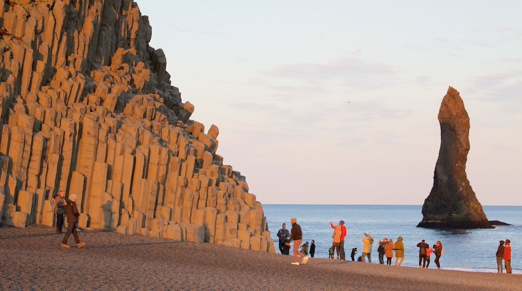 Reynisdrangar featuring general coastal views and a sunset as well as a large group of people