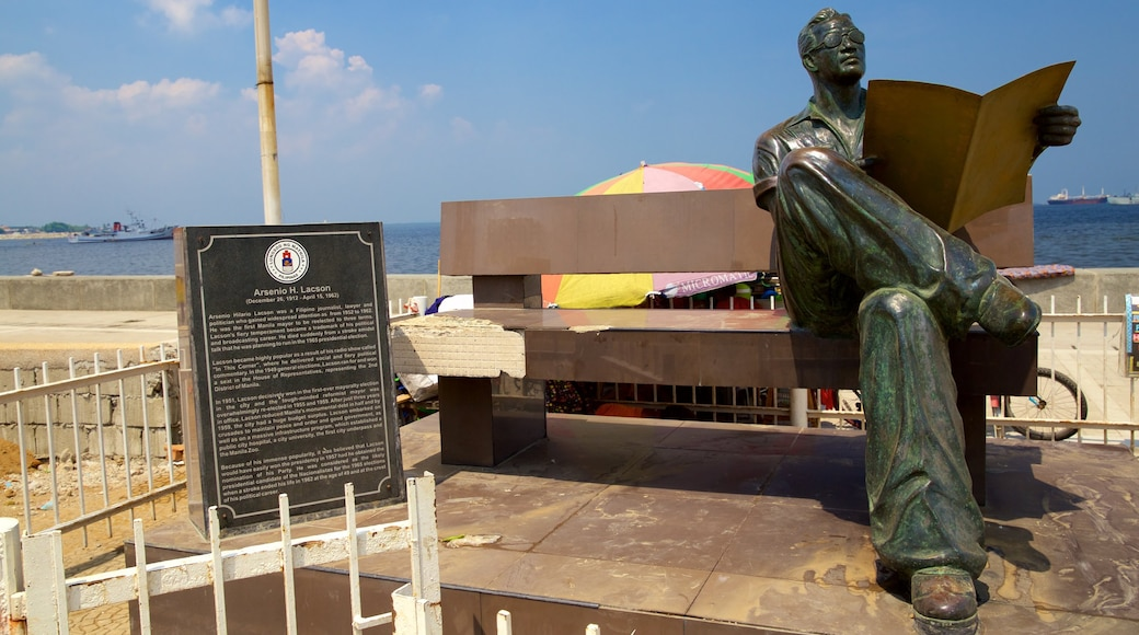 Manila Bay featuring a statue or sculpture and signage