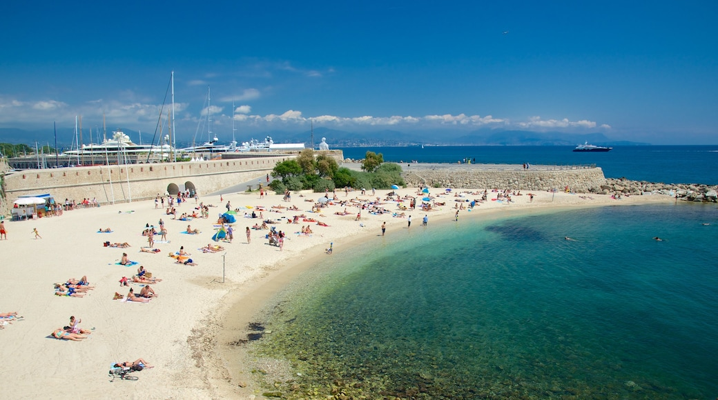 Antibes which includes a sandy beach as well as a large group of people