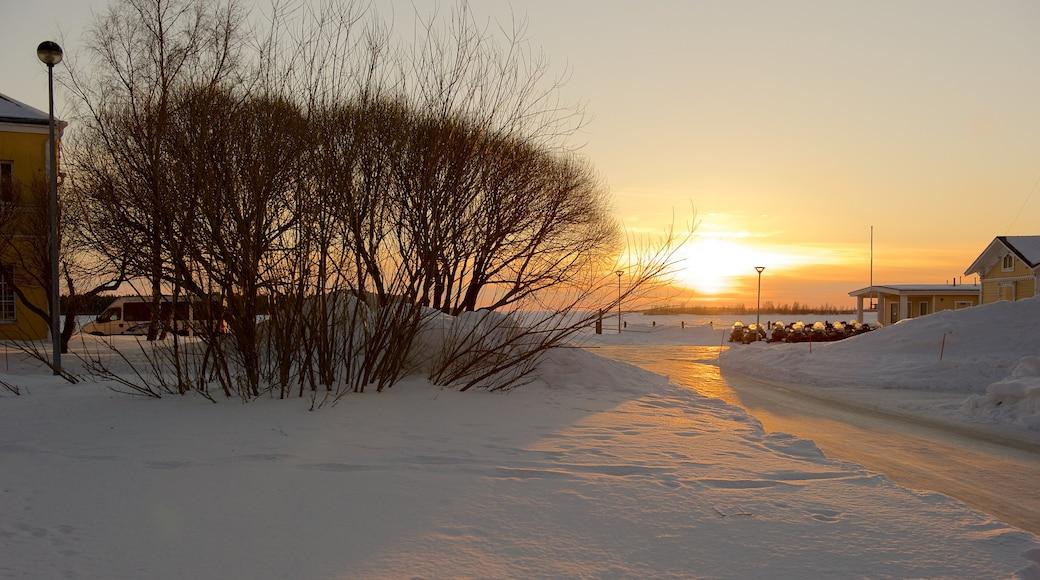 Kemi joka esittää pieni kaupunki tai kylä, lunta ja auringonlasku