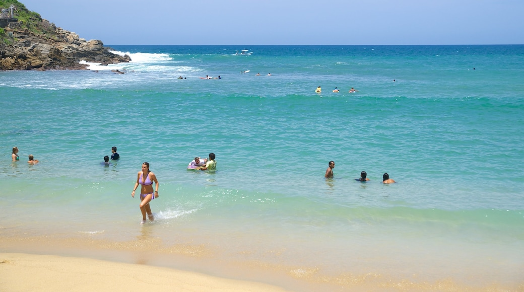 Carrizalillo Beach featuring swimming and a sandy beach as well as a large group of people