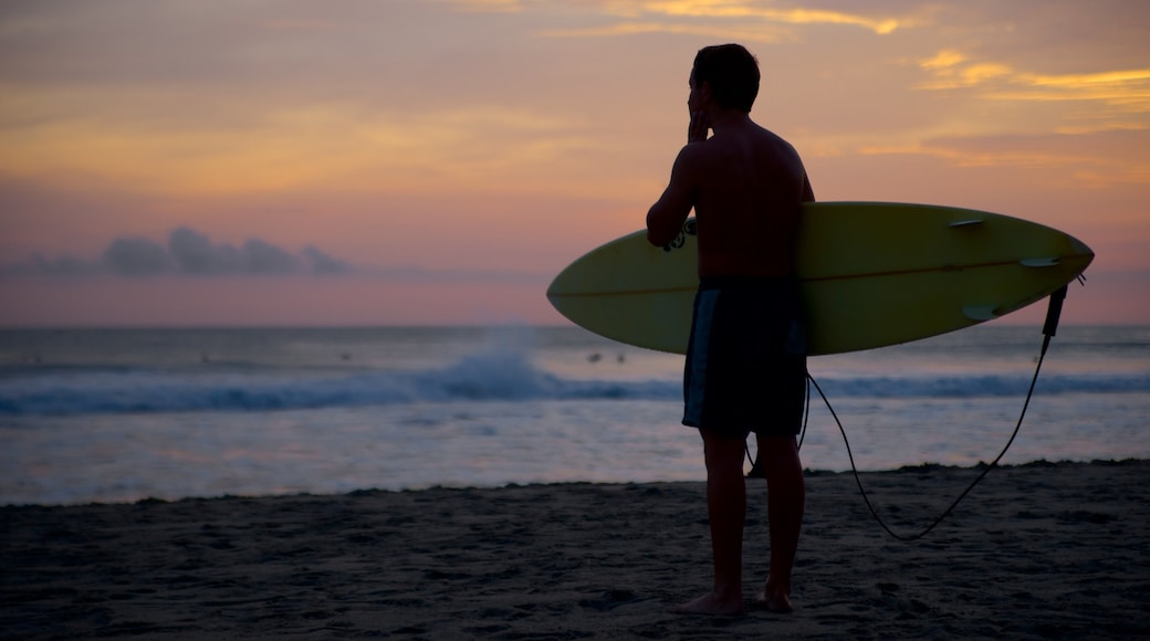 Puerto Escondido que incluye surf, una puesta de sol y una playa de arena