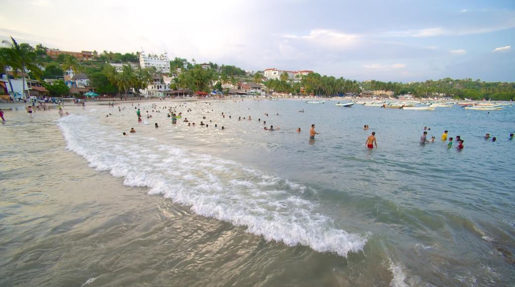 Puerto Escondido que incluye olas, una ciudad costera y paseos en lancha