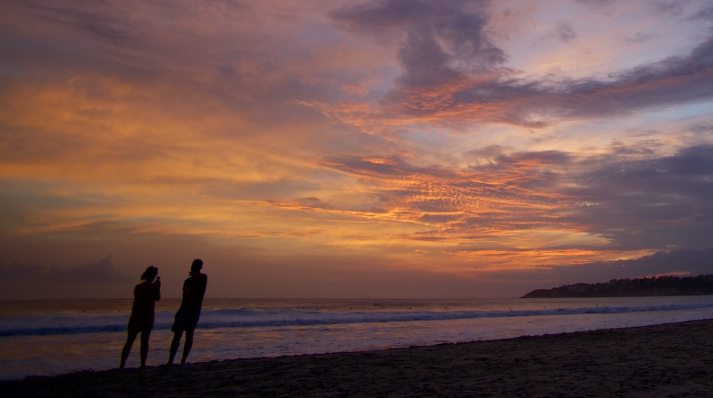 Zicatela Beach which includes a sunset and a sandy beach as well as a couple