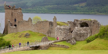 Urquhart Castle showing a lake or waterhole and building ruins