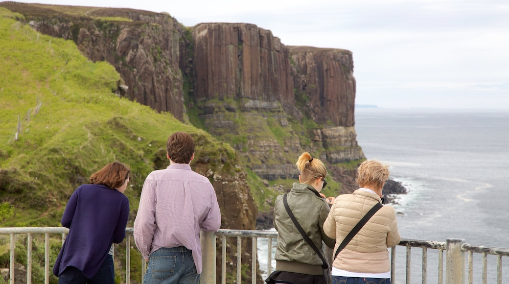 Kilt Rock showing rugged coastline and views as well as a family