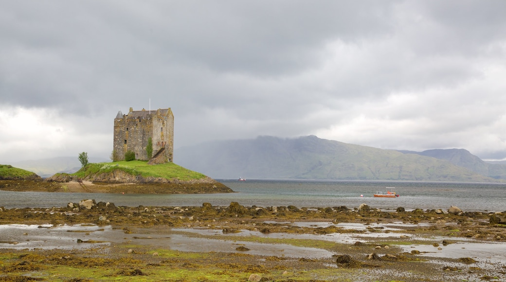 Castle Stalker featuring heritage architecture, château or palace and a lake or waterhole
