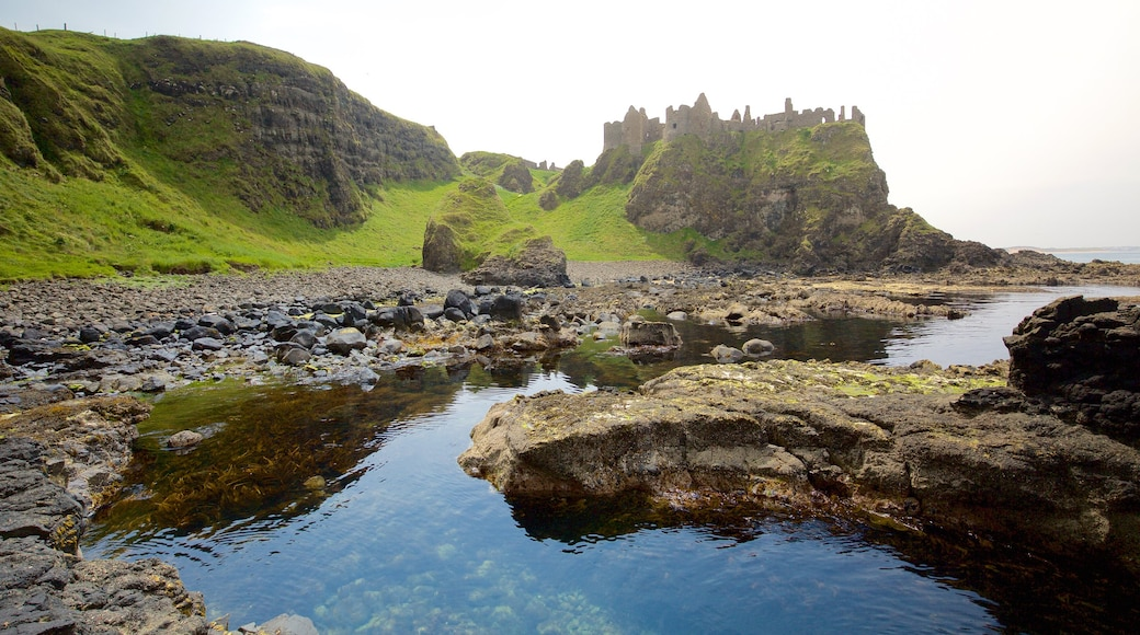 Dunluce Castle which includes rocky coastline, heritage architecture and building ruins