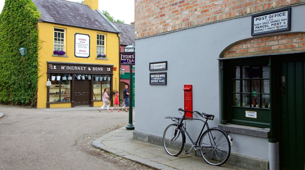 Bunratty Castle and Folk Park showing signage and street scenes as well as a small group of people
