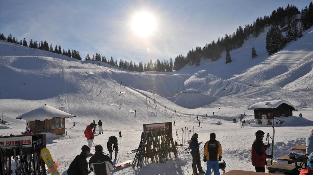 Spitzingsee welches beinhaltet Schnee und Skifahren sowie kleine Menschengruppe
