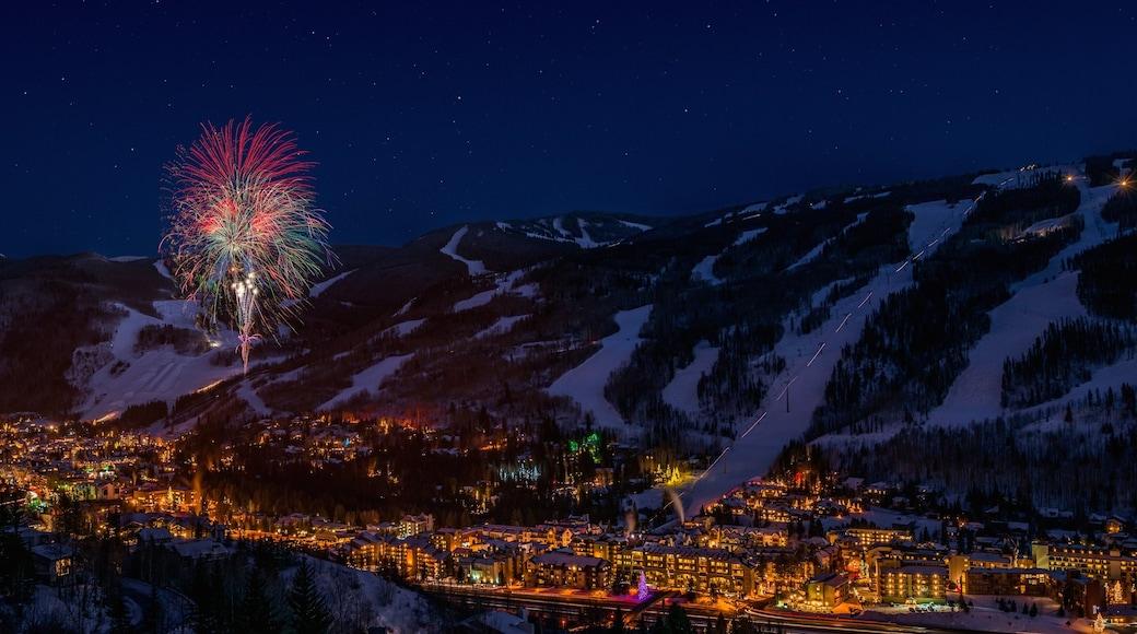 Vail som inkluderar en liten stad eller by, nattliv och snö