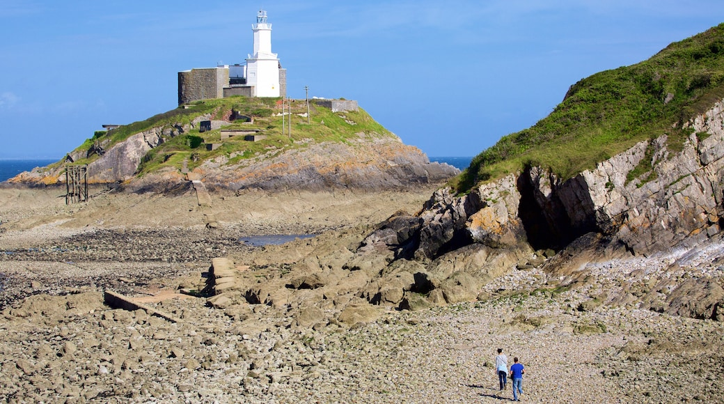 Mumbles Lighthouse featuring a pebble beach, mountains and a lighthouse