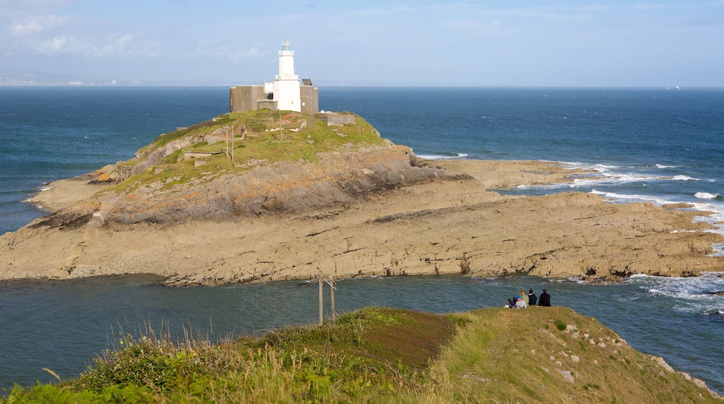 Mumbles Lighthouse featuring a lighthouse, rugged coastline and mountains