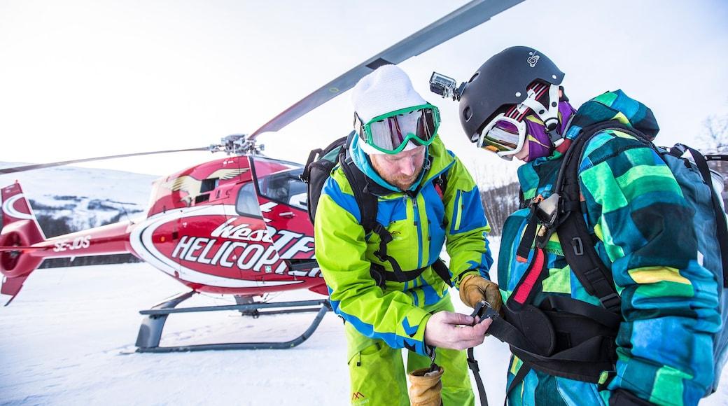 Björkliden Fjällby som inkluderar snö och ett flygplan såväl som en liten grupp av människor