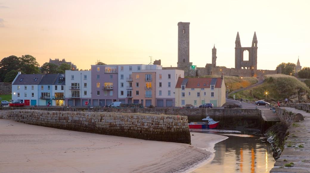 St. Andrew\'s Cathedral som visar en strand, en kuststad och en solnedgång