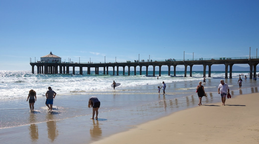 Manhattan Beach featuring hiking or walking and a sandy beach as well as a small group of people