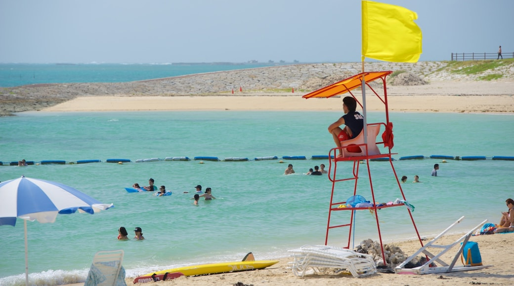 Okinawa showing a beach and swimming as well as a large group of people