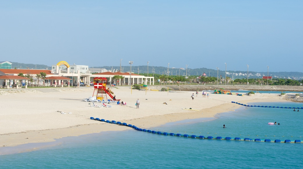 Okinawa showing swimming, a sandy beach and a coastal town