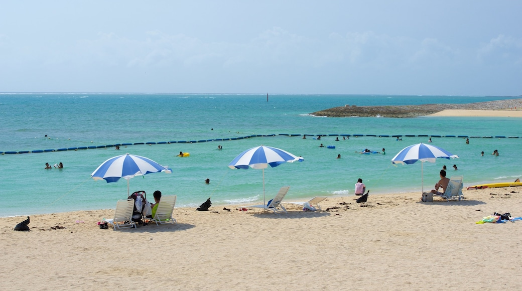 Okinawa which includes a sandy beach and swimming as well as a large group of people