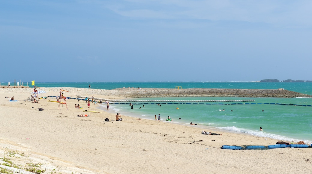 Okinawa which includes swimming and a sandy beach as well as a large group of people