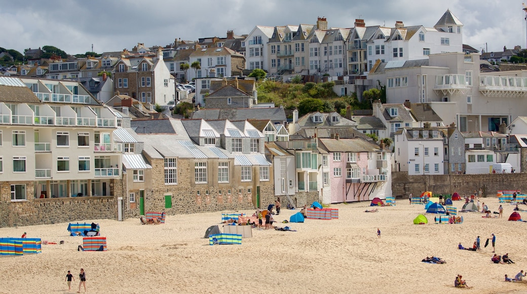 Porthmeor Beach showing a beach and a coastal town as well as a large group of people