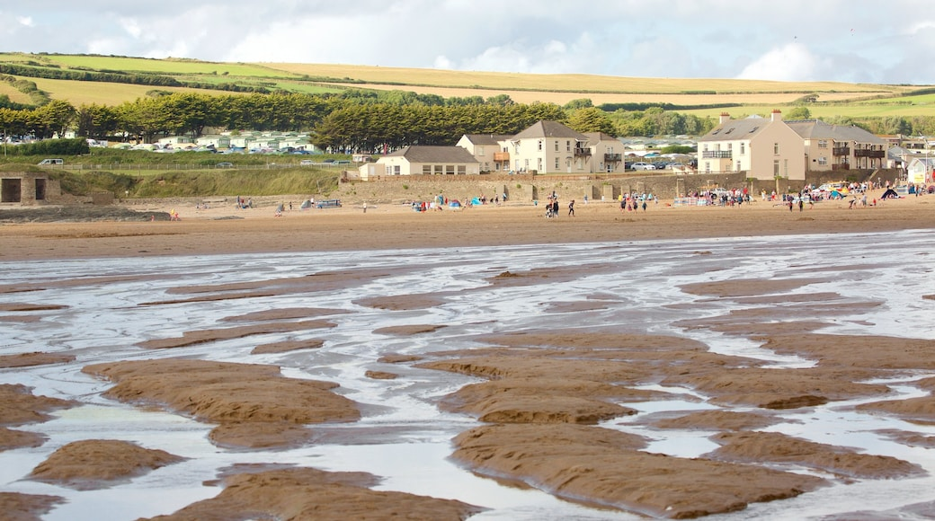 Croyde which includes a coastal town and a sandy beach as well as a large group of people