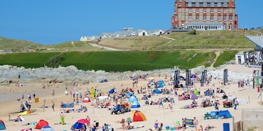 Fistral Beach showing a sandy beach and a coastal town as well as a large group of people