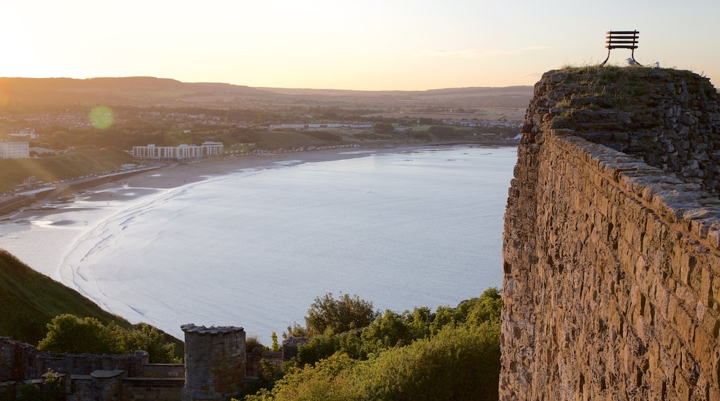 Scarborough Castle showing a sandy beach, a sunset and heritage elements