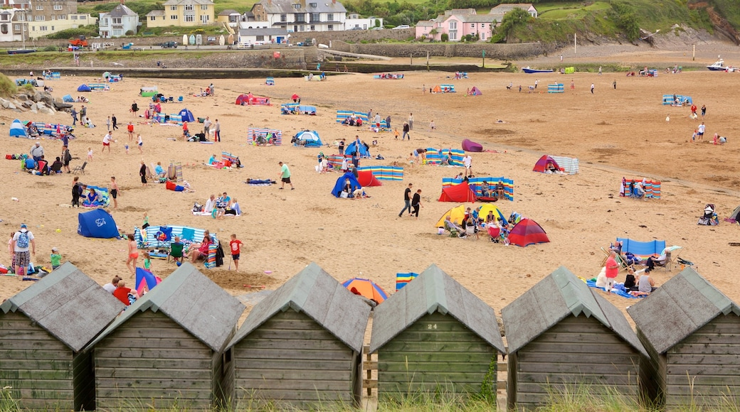 Bude Beach which includes a house and a sandy beach as well as a large group of people