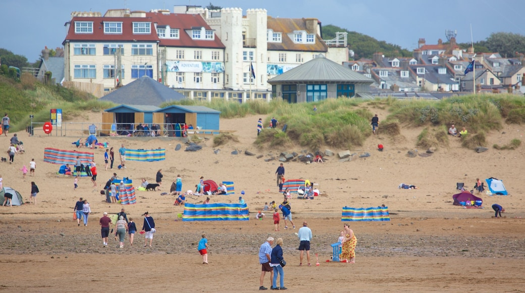 Bude Beach featuring a beach and a coastal town as well as a large group of people