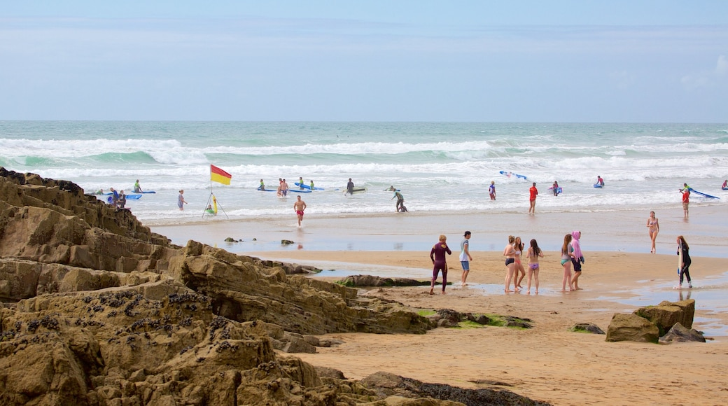 Bude Beach featuring rugged coastline and a sandy beach as well as a small group of people