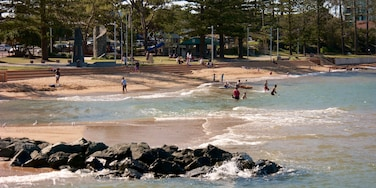 Redcliffe featuring waves and a sandy beach as well as a small group of people