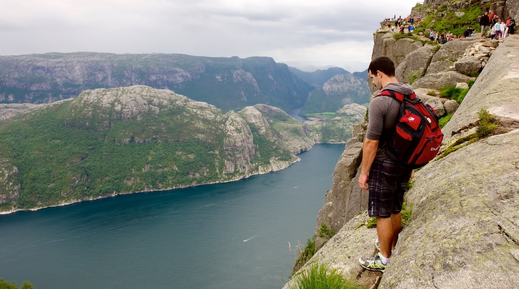 Preikestolen featuring a lake or waterhole and mountains as well as an individual male
