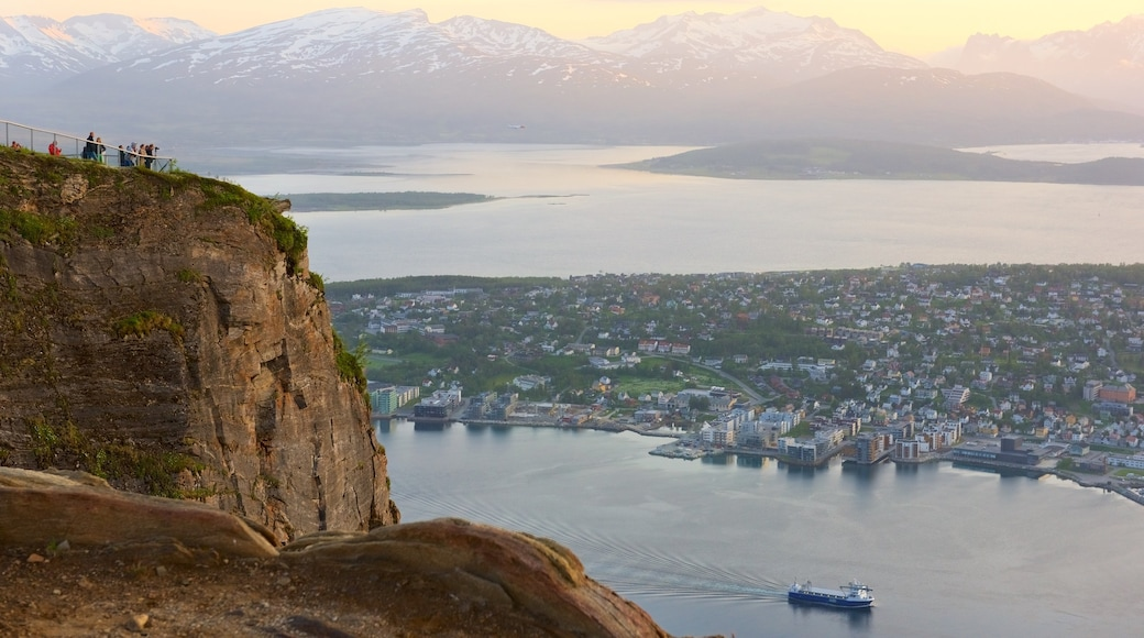 Tromso which includes a lake or waterhole, a sunset and a small town or village
