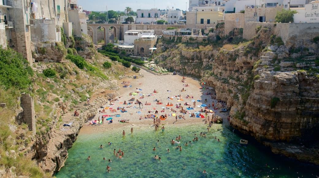 Polignano a Mare som viser sandstrand og klippelandskap i tillegg til en stor gruppe med mennesker