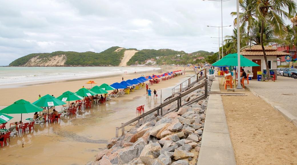 Praia de Ponta Negra caracterizando uma praia e paisagens litorâneas assim como um pequeno grupo de pessoas