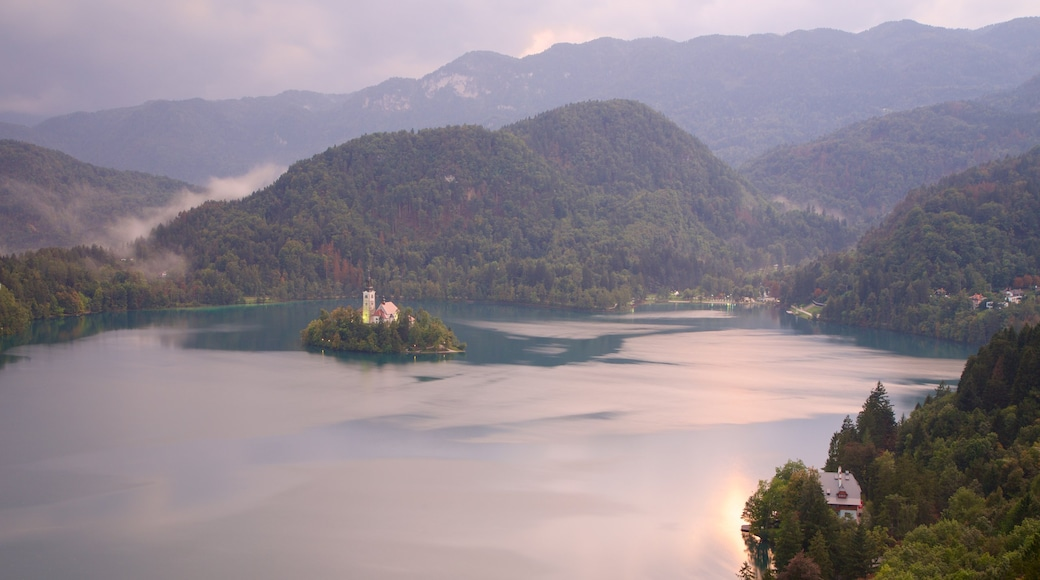 Lake Bled showing a lake or waterhole, mist or fog and mountains