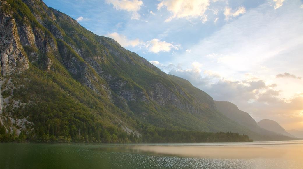 Bohinjsjön som visar en sjö eller ett vattenhål, berg och en solnedgång