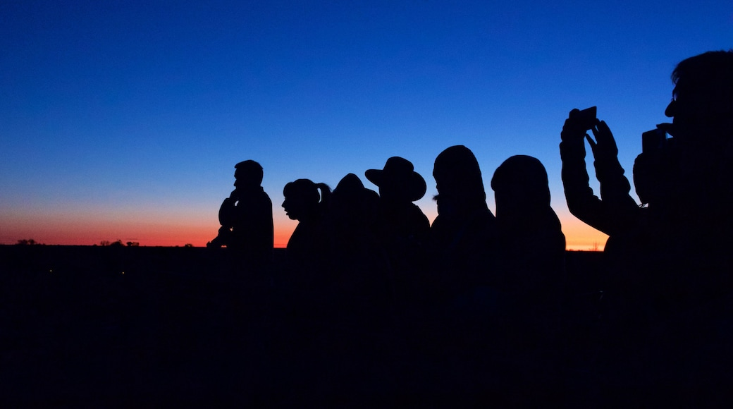 Uluru featuring a sunset and desert views as well as a small group of people