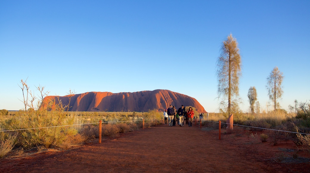 Uluru which includes landscape views and desert views as well as a small group of people